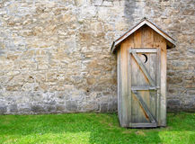 Rustic outhouse and vintage stone wall Stock Photo