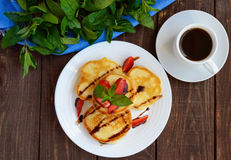 Rustic pancakes with fresh strawberries and chocolate on a white plate and cup of coffee. Stock Image