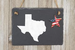 A rustic patriotic Texas state chalkboard. A retro chalkboard with a vintage USA star hanging and the state map of Texas on weathered wood background royalty free stock photo