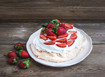Rustic Pavlova cake with fresh strawberries and whipped cream ov Royalty Free Stock Photography