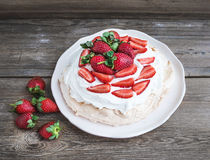 Rustic Pavlova cake with fresh strawberries and whipped cream ov Stock Photography