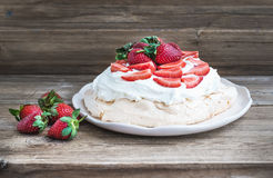 Rustic Pavlova cake with fresh strawberries and whipped cream ov Stock Image
