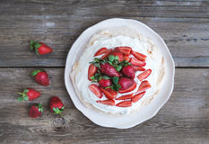 Rustic Pavlova cake with fresh strawberries and whipped cream ov Royalty Free Stock Images