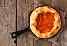 Rustic peach tart in cast iron skillet on old wood Royalty Free Stock Image