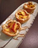 Rustic peach tarts. Displayed on autumn themed pottery Stock Image