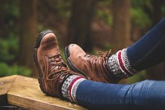 A rustic photo of hiking boots with a forest background. royalty free stock image