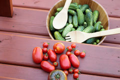 Rustic pickings of tomatoes and cucumbers Royalty Free Stock Photography