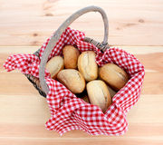 Rustic picnic basket of fresh bread rolls. On a pine table Stock Image