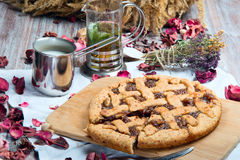 Rustic pie is on the board. On a background of cups of tea and milk Royalty Free Stock Photography