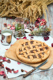 Rustic pie is on the board. On a background of cups of tea and milk Royalty Free Stock Images