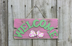 Rustic pink welcome sign with daisies and hearts hanging on wooden door royalty free stock image