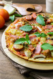 Rustic pizza with becon, salami, mozzarella and basil. On wooden table royalty free stock images