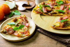 Rustic pizza with becon, salami, mozzarella and basil Royalty Free Stock Photography
