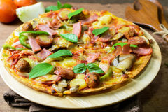 Rustic pizza with becon, salami, mozzarella and basil. On wooden table stock image