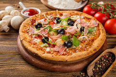Rustic pizza with ingredients, top view. Rustic pizza with mozzarella, olives, basil and ham. Served on vintage wooden table stock photography