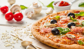 Rustic pizza with ingredients, top view. Rustic pizza with mozzarella, olives, basil and ham. Served on vintage wooden table stock photos
