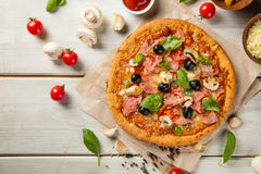 Rustic pizza with ingredients, top view. Rustic pizza with mozzarella, olives, basil and ham. Served on vintage wooden table royalty free stock photo