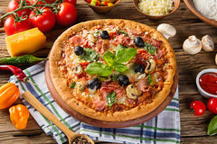 Rustic pizza with ingredients, top view. Rustic pizza with mozzarella, olives, basil and ham. Served on vintage wooden table stock image