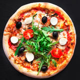 Rustic pizza with mozzarella, four cheese, olives and arugula t. Op view with copy space for restaurant menu on black background royalty free stock images