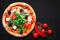 Rustic pizza with mozzarella, four cheese, olives and arugula t. Op view with copy space for restaurant menu on black background royalty free stock photos