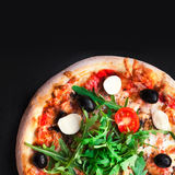 Rustic pizza with mozzarella, four cheese, olives and arugula t. Op view with copy space for restaurant menu on black background royalty free stock image