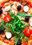 Rustic pizza with mozzarella, four cheese, olives and arugula t. Op view with copy space for restaurant menu on black background stock photography
