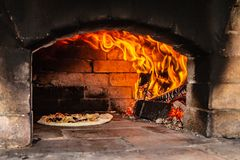 Fire in rustic pizza oven. Rustic pizza oven made of red bricks with pizza inside and fire royalty free stock images