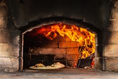 Fire in rustic pizza oven. Rustic pizza oven made of red bricks with pizza inside and fire stock photos