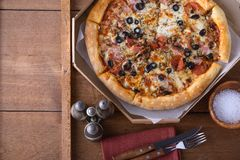 Rustic pizza with pepperoni sausage, mozzarella, olives and basil. Top view with copy space stock images