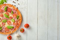 Rustic pizza with salami, mozzarella, cherry and a view of the basilica with a copy of the space. Sauce sausage served red mediterranean above pepper table royalty free stock photo