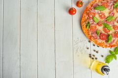 Rustic pizza with salami, mozzarella, cherry and a view of the basilica with a copy of the space. Sauce sausage served red mediterranean above pepper table royalty free stock images