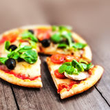 Rustic pizza with salami, mozzarella, olives and basil top view. Rustic pizza with mozzarella, olives and basil top view with copy space stock photos