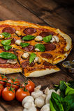 Rustic pizza with salami, mozzarella and spinach. On a clay plate royalty free stock photo