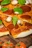 Rustic pizza with salami, mozzarella and spinach. On a clay plate royalty free stock photography