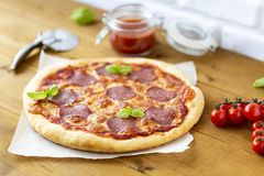 Rustic pizza with salami, mozzarella, olives and basil. Rustic pizza with salami, mozzarella, tomato, olives and basil stock image