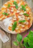 Rustic pizza topped with fresh basil leaves Royalty Free Stock Photos