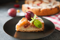 Rustic plum cake garnished with gooseberry and mint. Homemade summer plum cake garnished with gooseberry and mint on dark background Stock Photos
