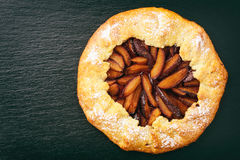 Rustic plum pie on black background. royalty free stock photo