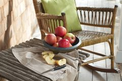 Rustic porch with apples, rocking chair. Closeup of country porch outdoors with apple still life on rustic table and antique rocking chair. Cedar shingles in Stock Photo