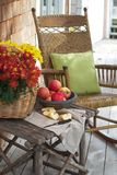 Rustic porch with apples and rocking chair. Closeup of country porch outdoors with apple still life on rustic table and antique rocking chair. Cedar shingles in Stock Photos