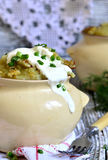 Rustic potato casserole with sour cream in a clay pot. Royalty Free Stock Photos