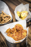Rustic potato chips and other snack food on table Stock Images