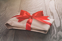 Rustic present box with red ribbon on wood table Royalty Free Stock Photos