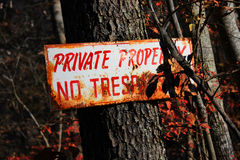 Rustic Private Property Sign. A rustic private property sign in a wooded area with red leaves Stock Images