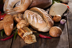 Rustic products on wood table. Sliced cheese near vegetables and bread on wood table Stock Photography