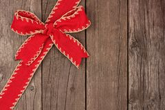 Red Christmas bow and ribbon corner border on old wood Royalty Free Stock Photos