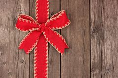 Red Christmas bow and ribbon side border on old wood Royalty Free Stock Image