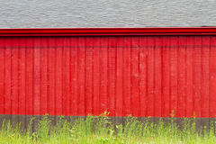 Rustic Red and Gray Building Backdrop. Backdrop of side of a building with bright red, vertical wood planks and gray tile roof filling frame.  Wild plants at Royalty Free Stock Photography