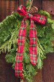 Rustic red and green flannel bow on Christmas wreath. royalty free stock photography