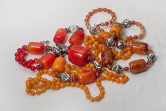Rustic red jewelery. Jewellery made ​​of onyx and plastic red coral and orange shades royalty free stock photography